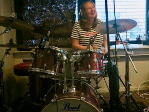 Glad kvinne spiller trommer med trommelærer